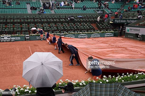 TOPSHOT Workers cover the court as play is interrupted due to rain at the Roland Garros 2016 French Tennis Open in Paris on May 31 2016 / AFP / Eric...