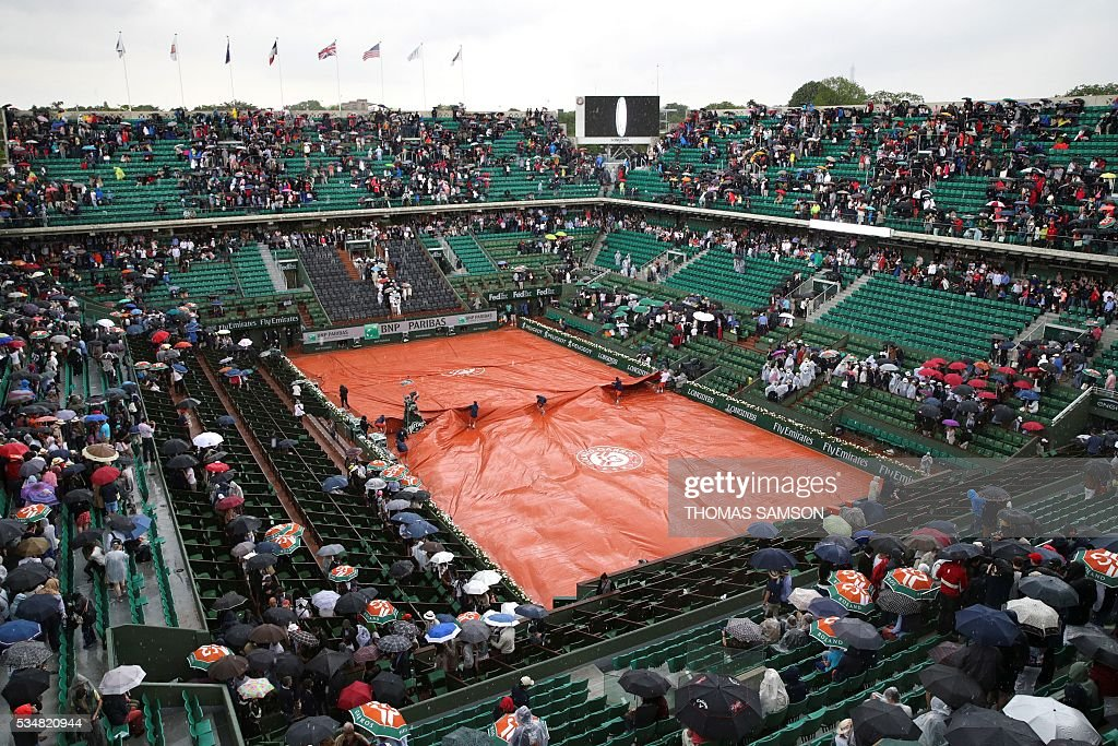 Workers cover the court during their women's third round match between US player Serena Williams and France's Kristina Mladenovic at the Roland Garros 2016 French Tennis Open in Paris on May 28, 2016. / AFP / Thomas SAMSON