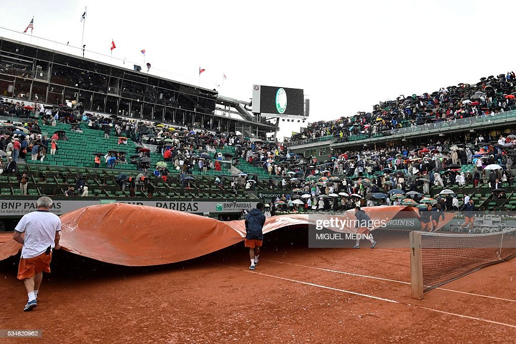 Workers cover the court during their women's third round match between US player Serena Williams and France's Kristina Mladenovic at the Roland Garros 2016 French Tennis Open in Paris on May 28, 2016. / AFP / MIGUEL