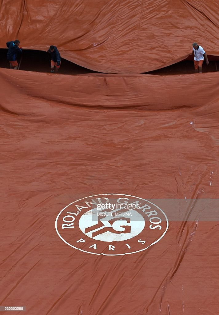 Workers cover the tarp as play is interrupted due to rain during the women's fourth round match between Poland's Agnieszka Radwanska and Bulgaria's Tsvetana Pironkova at the Roland Garros 2016 French Tennis Open in Paris on May 29, 2016. / AFP / MIGUEL