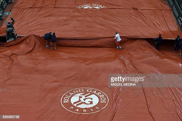 Workers cover the tarp as play is interrupted due to rain during the women's fourth round match between Poland's Agnieszka Radwanska and Bulgaria's...