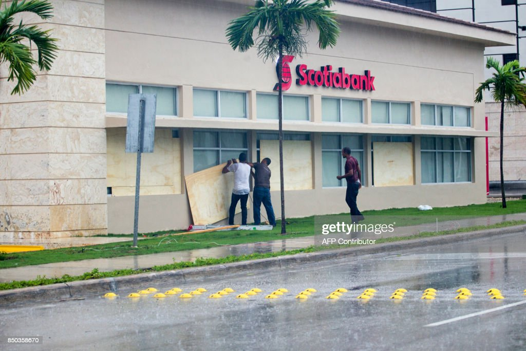 Workers cover the windows of a bank in Punta Cana, in the Dominican Republic, as Hurricane Maria approaches on September 20, 2017. The government of the Dominican Republic told people to stay home from their public and private sector jobs on Thursday, when the hurricane is expected to hit the island. / AFP PHOTO / Erika SANTELICES