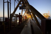 Workers cross a connecting bridge on the Petroleos Mexicanos PolA Platform complex located on the continental shelf in the Gulf of Mexico 70...