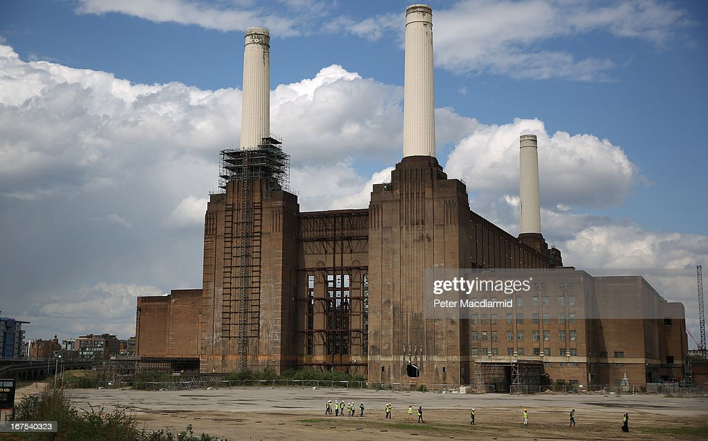 Workers cross an empty area of land in front of Battersea power station on April 26, 2013 in London, England. Built in the 1930s, with an identical second section added in the 1950s, the Grade II* listed building last generated electricity in 1983. The 15.7 hectare site on the south bank of The River Thames is being re-developed. Over the next 11 years 3400 homes, office space and a theatre will be built in and around the power station which is still the largest brick building in Europe.