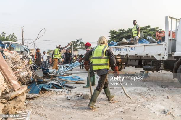 Workers demolish an illegal structure as Benin security forces stand at a busy intersection during an evacuation in downtown Cotonou on January 27...