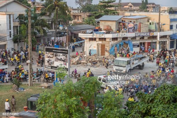 Workers demolish an illegal structure at a busy intersection during an evacuation in downtown Cotonou on January 27 2017 On the streets of Benin's...