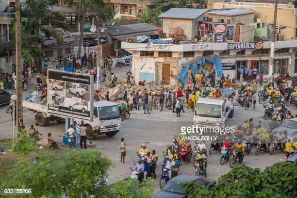 Workers demolish an illegal structure at a busy intersection in downtown Cotonou on January 27 2017 On the streets of Benin's economic capital of...