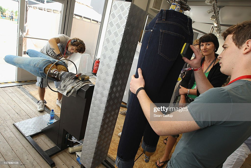 Workers demonstrate custom denim fading at the Laboratorio stand at the 2012 Bread & Butter fashion trade fair at former Tempelhof Airport on July 6, 2012 in Berlin, Germany. Bread & Butter is the world's largest trade fair for street fashion.