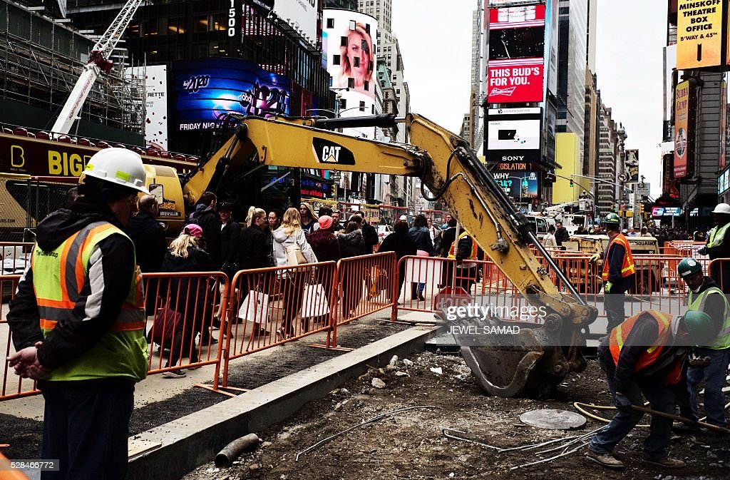 Workers dig to clear cement and soil to rebuild a footpath at the Times Square in New York on May 5, 2016. An increase in layoffs pushed US claims for unemployment insurance higher last week but the jobs market remains tight, Labor Department data showed. / AFP / Jewel SAMAD