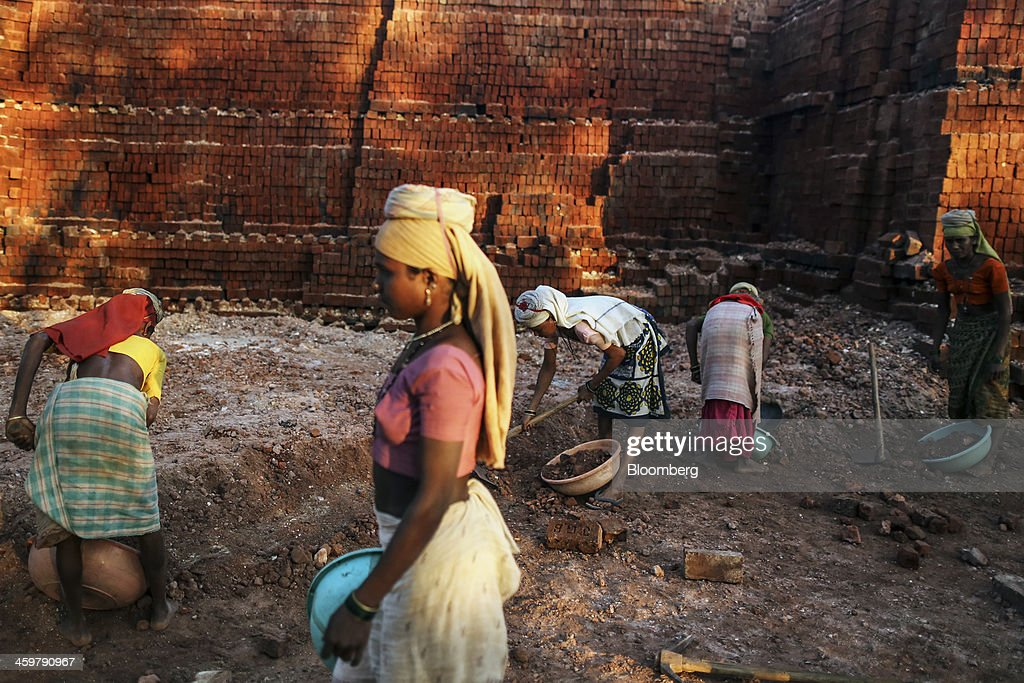 Workers dig up soil at a brick manufacturer's in Kainad, Maharashtra, India, on Saturday, Dec. 21, 2013. The construction of 600,000 kilometers (373,000 miles) of country roads, addition of 327 million rural phone connections and a rise in literacy to record levels since Prime Minister Manmohan Singh took office in 2004 has helped double the growth rate of Indias food output. Photographer: Dhiraj Singh/Bloomberg via Getty Images