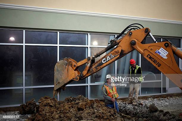 Workers direct an excavator at the construction site for Horizon Group Properties Inc's The Outlet Shoppes of the Bluegrass in Simpsonville Kentucky...