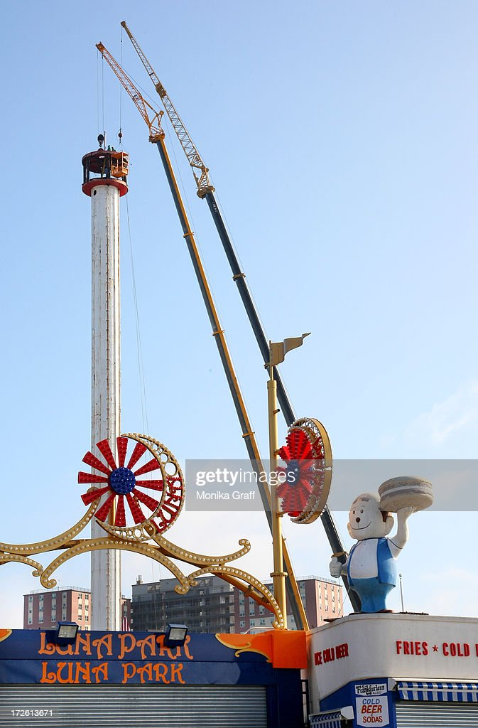 Workers disassemble the Astrotower as Luna Park remains closed in Coney Island on July 4, 2013 in the Brooklyn borough of New York City. Officials decided to close Luna Park and sections of the boardwalk while workers take down the amusement tower which was seen precariously swaying two days ago.