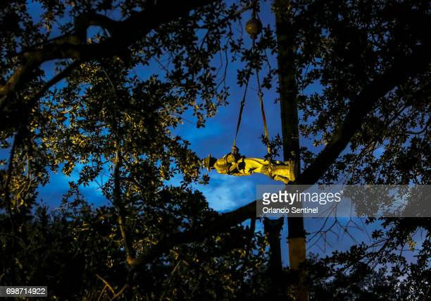 Workers disassemble the 'Johnny Reb' Confederate memorial statue at Lake Eola Park on Tuesday morning June 20 2017 The statue will later be...