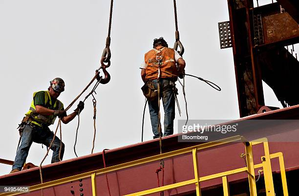 Workers disconnect a load of building materials after it was moved by a crane at the World Trade Center site in New York US on Tuesday Sept 8 2009...