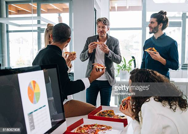 Workers  discussing concepts whilst eating pizza for a group meeting