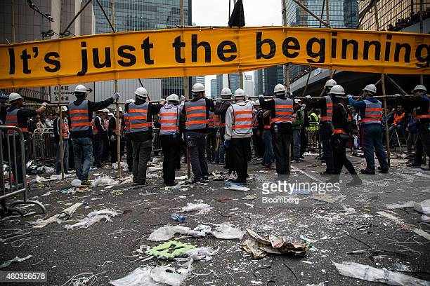 Workers dismantle a barricade erected by prodemocracy protesters with a banner reading 'It's Just The Beginning' near the Central Government Offices...