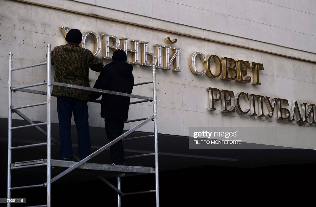 Workers dismantle the inscription written in the Ukranian language reading 'The Supreme Council of the Autonomous Republic of Crimea' on the Crimean parliament building in Simferopol, Crimea, on March 18, 2014. President Vladimir Putin has backed the approval of a draft agreement which would incorporate Ukraine's region of Crimea into Russian territory, according to an official instruction published today.