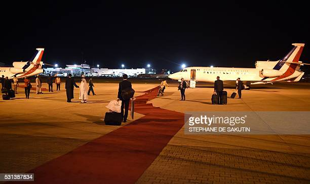 Workers display the red carpet prior the departure of the planes of the French delegation at the airport in Abuja on May 14 2016 Regional and Western...