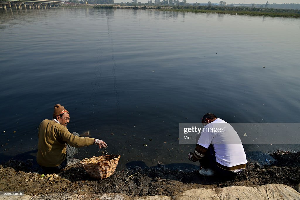 BJP worker doing Shramdaan (Swachh Yamuna Mission) at ITO Chhath Ghat on birthday of former PM Atal Bihari Vajpayee on December 25, 2015 in New Delhi, India.