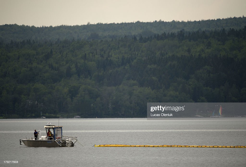 Workers drag an oil boom on Lac-MÈgantic Tuesday afternoon following the massive derailment that sent thousand of liters of oil into the lake and down the ChaudiËre River.