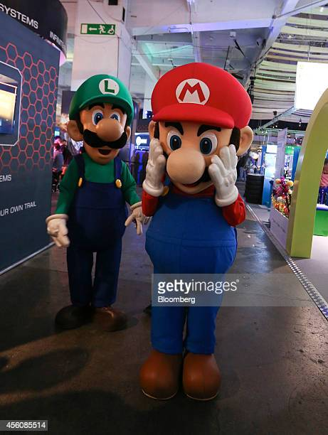 Workers dressed as Nintendo Co's Mario and Luigi characters pose for a photograph during the EGX gaming conference at Earls Court in London UK on...
