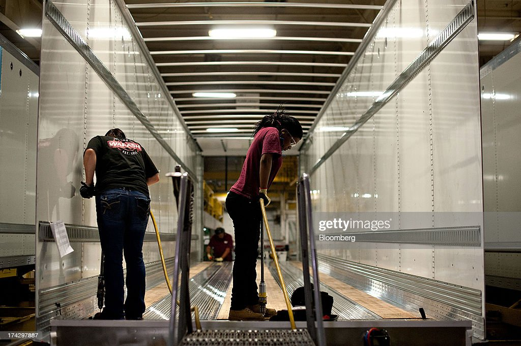 Workers drill holes to secure flooring to the frame of a semi trailer at the Wabash National Corp. facility in Lafayette, Indiana, U.S., on Monday, July 22, 2013. Wabash National Corp. is scheduled to release earnings figures on July 30. Photographer: Daniel Acker/Bloomberg via Getty Images