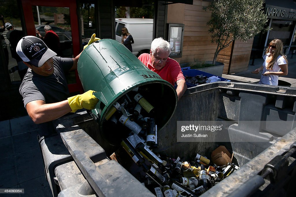Workers dump broken bottles into a dumpster following a 6.0 earthquake on August 24, 2014 in Napa, California. A 6.0 earthquake rocked the San Francisco Bay Area shortly after 3:00 am on Sunday morning causing damage to buildings and sending at least 70 people to a hospital with non-life threatening injuries.