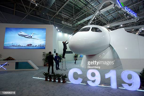 Workers dust off a model of a Commercial Aircraft Corp of China C919 airplane displayed at the Airshow China 2010 in Zhuhai Guangdong province China...