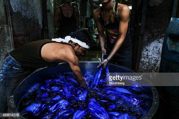 Workers dye fabrics in a metal vat at a workshop in the Dharavi slum area of Mumbai India on Monday Aug 11 2014 Almost a year after Reserve Bank of...