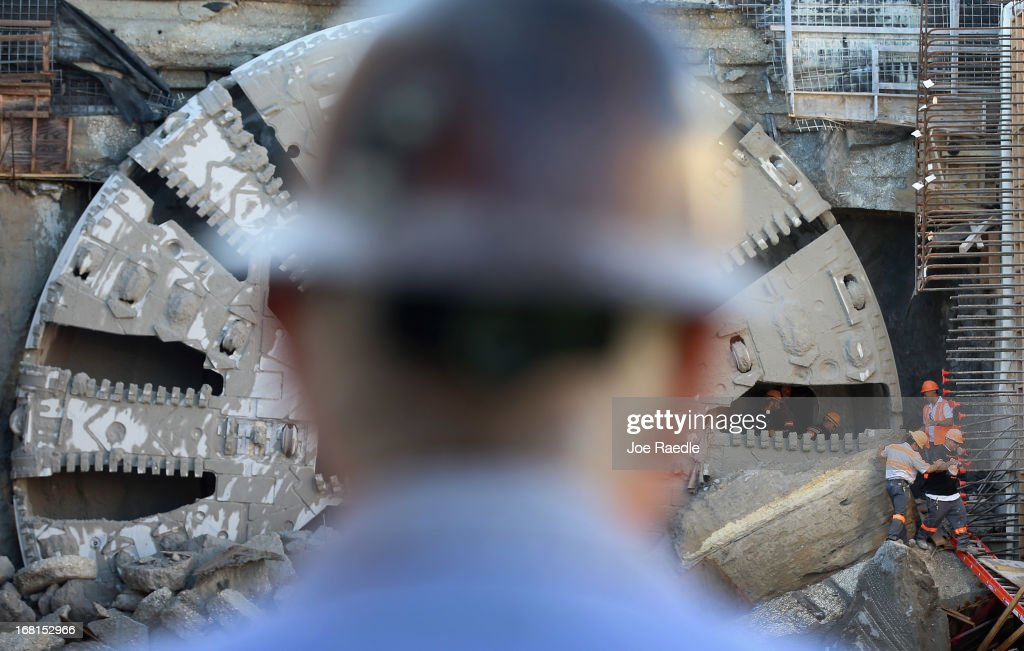 Workers emerge from behind the massive drill nicknamed Harriet after it broke through on Watson Island on May 6, 2013 in Miami, Florida. The emergence of the drill completed the second leg of the 13 month-old, billion dollar Miami Tunnel project, which when finished will connect the mainland to the Port of Miami.