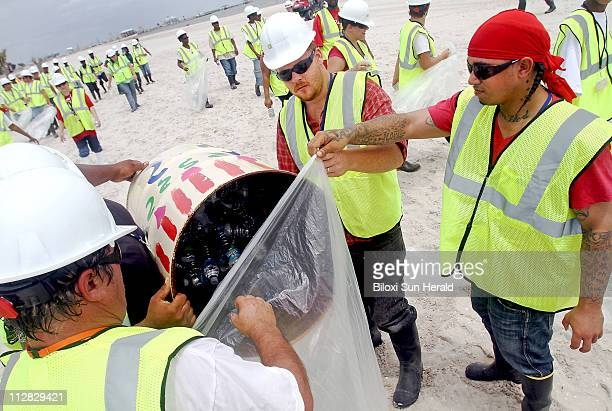Workers empty the trash cans on the beach while cleaning up after a training session on the beach in Pass Christian Mississippi on Tuesday June 22...