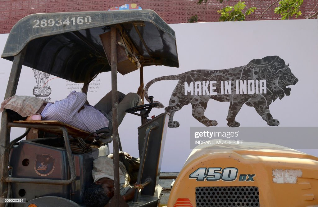 Workers enjoy a siesta during a break in work at the venue for the 'Make in India' showcase week in Mumbai on February 11, 2016. Over 190 companies, including national conglomerates and multinational corporations, 5,000 delegates from 60 countries, and leading industrialists including Ratan Tata and Mukesh Ambani will be participating in the maiden 'Make in India' showcase to be held in Mumbai from February 13-18. AFP PHOTO/ INDRANIL MUKHERJEE / AFP / INDRANIL MUKHERJEE