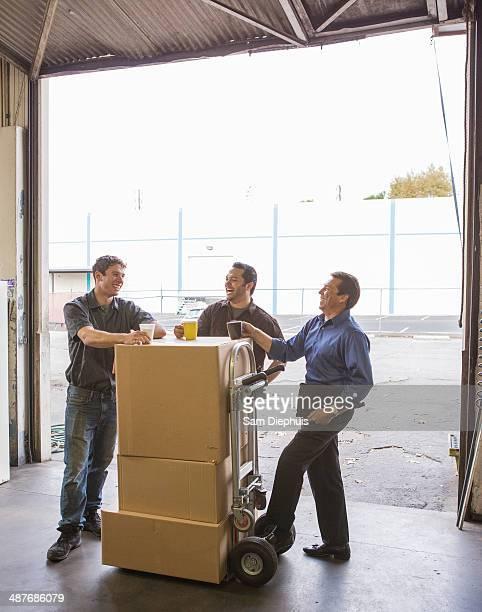 Workers enjoying coffee break at warehouse loading dock