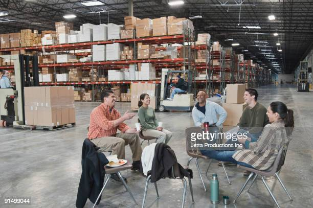 Workers enjoying coffee break in warehouse