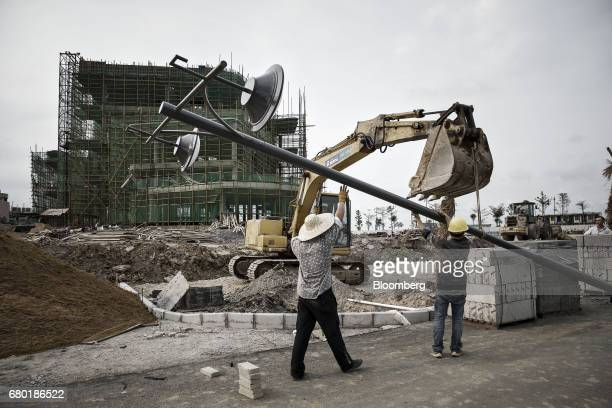 Workers erect a lamp post near the under construction Beauty Farm International Medical AntiAging Center inside the Hainan Boao Lecheng...