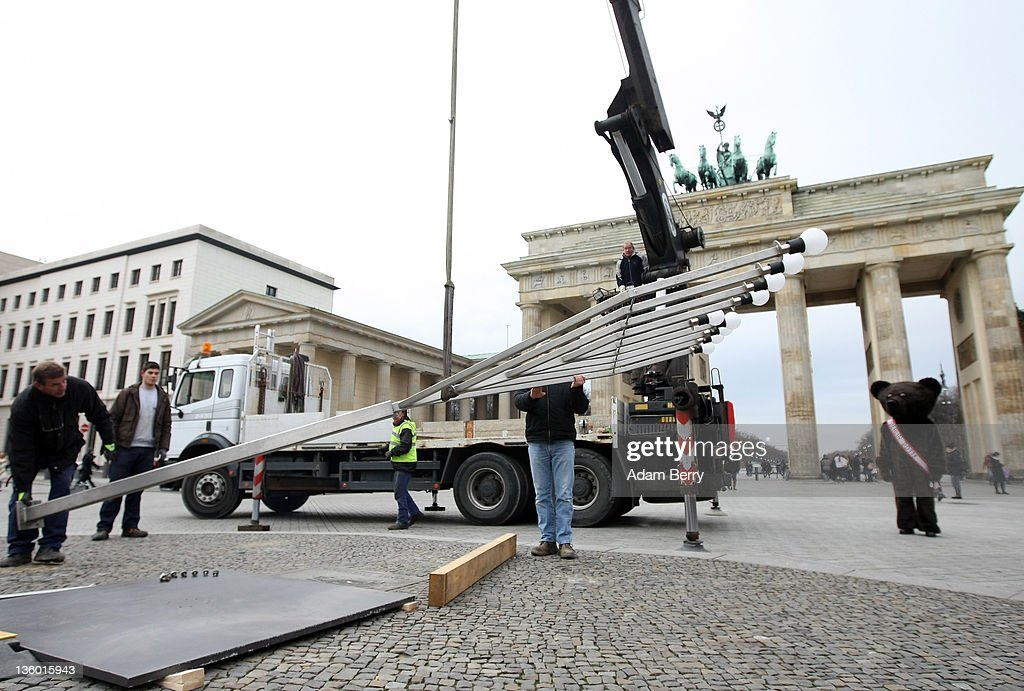 Workers erect a large nine-armed candleholder, a Hannoukiah, or Menorah, ahead of the start of the eight-day-long and annual Jewish Festival of Lights known as Chanukah, as a street performer dressed as the mascot of the city of Berlin, the Berliner Bear, looks on in front of the Brandenburg Gate on December 20, 2011 in Berlin, Germany. The festival marks the rebellion of Maccabee Jews against the Greeks in 165 BC, which some believers say included a number of miracles pointing to divine providence.