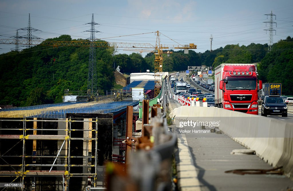 Workers erect a new bridge at a construction site along the A45 highway on August 20 2015 near Hagen Germany with traffic flowing along next to the...