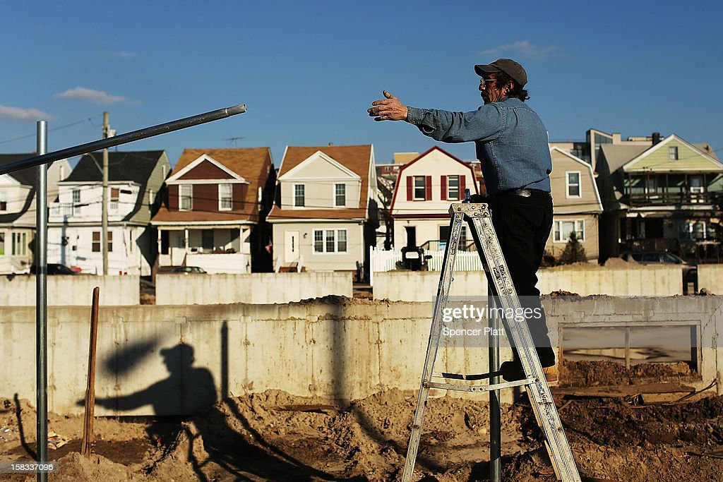 Workers erect a new fence near the beach in Rockaway on December 13, 2012 in New York City. Much of the Rockaway neighborhood is still suffering the effects of Hurricane Sandy which caused extensive damage to parts of New York, New Jersey and Connecticut. Thousands of Rockaway residents and business owners are still unable to return to their properties while electricity remains sporadic in many neighborhoods.