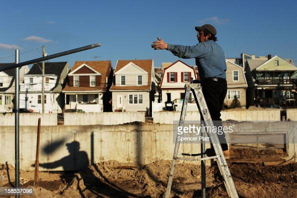 Workers erect a new fence near the beach in Rockaway on December 13 2012 in New York City Much of the Rockaway neighborhood is still suffering the...