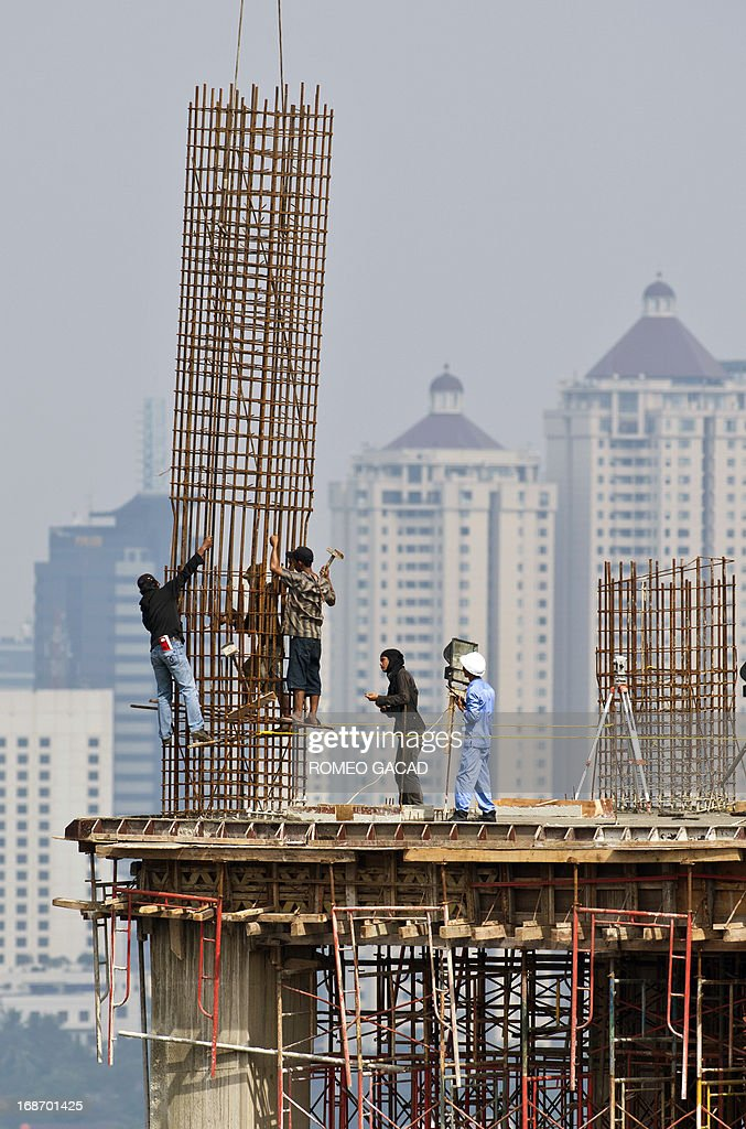 Workers erect an iron reinforcement column at a high rise office building under construction in Jakarta on May 14, 2013. Indonesia held its key interest rate at 5.75 percent on May 14, 2013 for the 15th consecutive month after the economy expanded at the slowest pace for more than two years in the first quarter.
