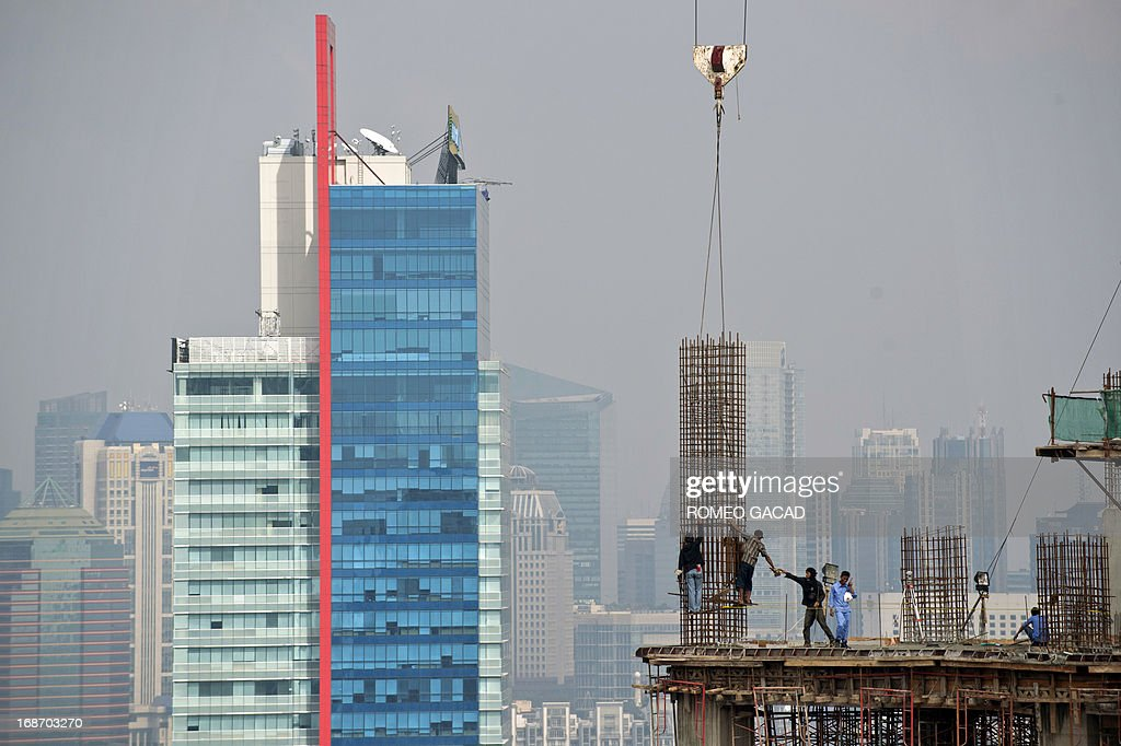Workers erect an iron reinforcement column at a high rise office building under construction in Jakarta on May 14, 2013. Indonesia held its key interest rate at 5.75 percent on May 14, 2013 for the 15th consecutive month after the economy expanded at the slowest pace for more than two years in the first quarter. AFP PHOTO / ROMEO GACD