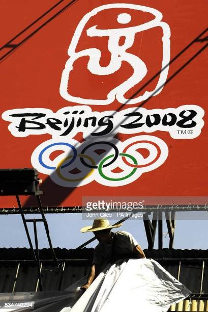 Workers erect giant posters for the Beijing Olympics in Macau China