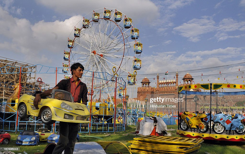 Workers erecting merrygoround as a Ramlila preparation at Nav Shri Dharmik Lila Committee at Red Fort on October 3 2013 in New Delhi India Ramlila is...