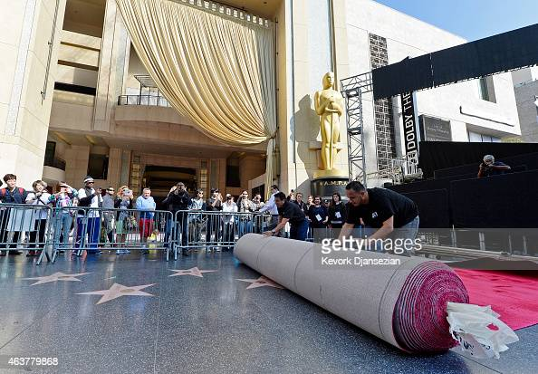Workers Ernest Jauregui and Rodolfo Morales roll out the ceremonial red carpet over the Hollywood Walk of Fame stars on Hollywood Boulevard in...
