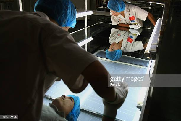 Workers examine the photovoltaic board product at the plant of Tianwei Yingli Green Energy Resources Co Ltd on June 24 2009 in Baoding China China's...