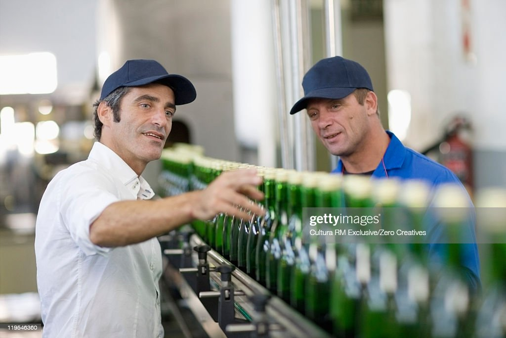 Workers examining bottles in factory : Stock Photo