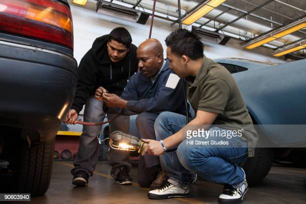 Workers examining car in auto body shop
