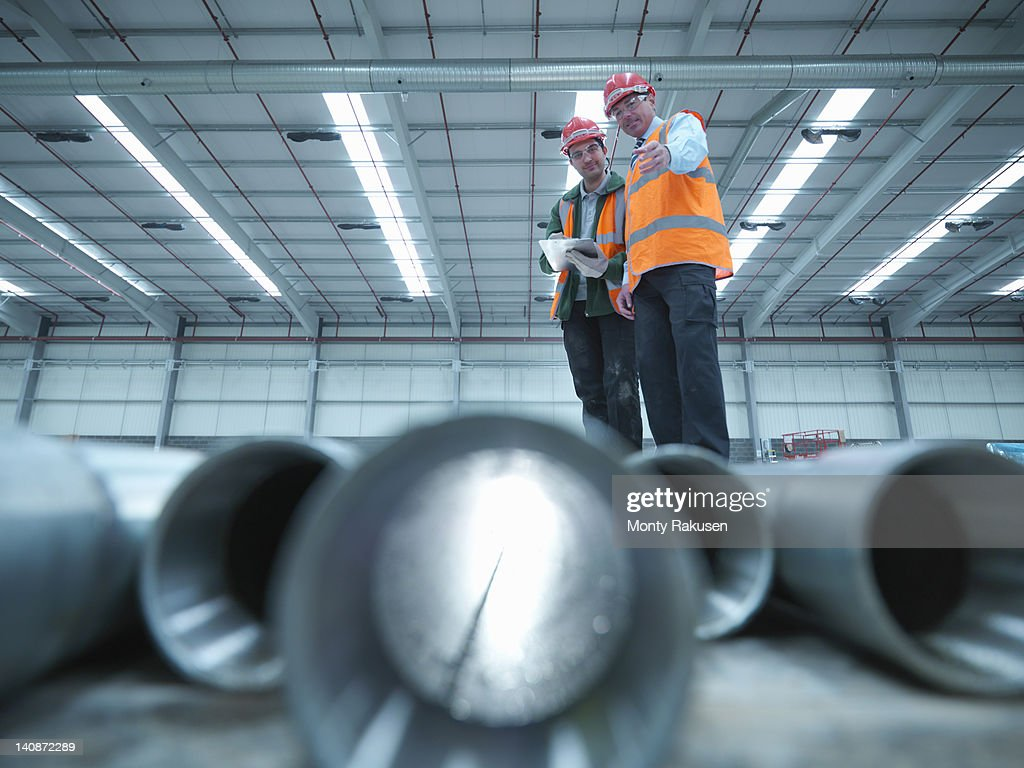 Workers examining pipes in warehouse