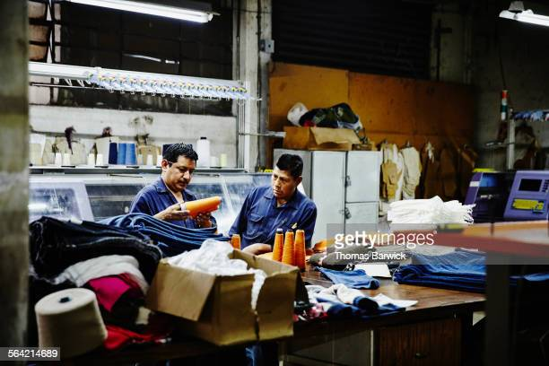 Workers examining spools of thread in factory
