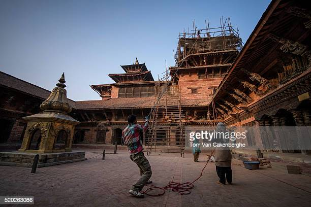 Workers experienced in traditional Nepali style construction pull up materials during the reconstruction of the major Taleju temple tower at the...